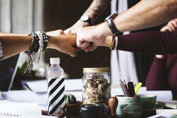 Symbolisches Foto für Geschäftsabschluss: fünf Menschen strecken ihre Arme gemeinsam zu einer Mitte